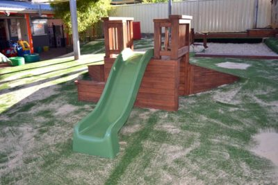 Timber platform with mound slide over synthetic grass (front view)